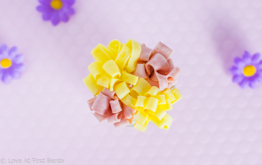 Ham & Egg Flowers - Learn exactly how to make these classic bento box space fillers with the help of a video tutorial. They taste delicious, and can be prepared in mere minutes. No more empty spaces in your bento! | www.loveatfirstbento.com