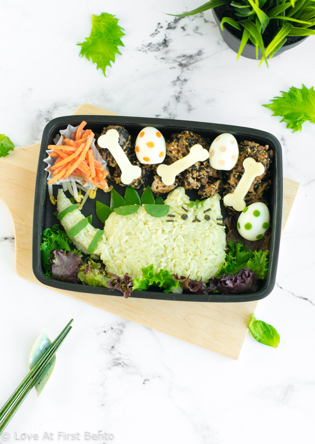 Pusheenosaurus Bento Box - Pusheen the Cat goes prehistoric in this dinosaur themed character bento box! Learn the trick that makes shaping the rice easier, + how to naturally dye your rice green, at www.loveatfirstbento.com