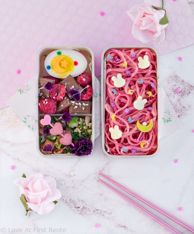 Sailor Moon Noodles Bento Box - Learn exactly how to make this gorgeous character bento box that's fit for a moon princess! Featuring super easy naturally colored pink noodles, an edible mini Moon Stick, and an easy-to-follow video tutorial. Get the recipe at loveatfirstbento.com