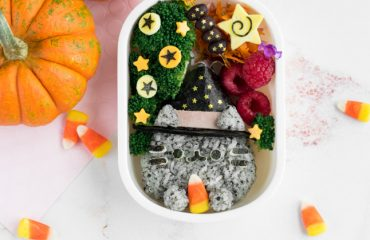 """Witch Pusheen Halloween Bento Box - Make a Halloween lunch that's so cute, it's scary, thanks to the always adorable Pusheen the Cat! You won't be able to guess the 2 kitchen """"magic tricks"""" used to make preparing this bento way faster & easier. Get the step-by-step instructions + video tutorial for this bento at: loveatfirstbento.com   charaben, kyaraben, character bento"""