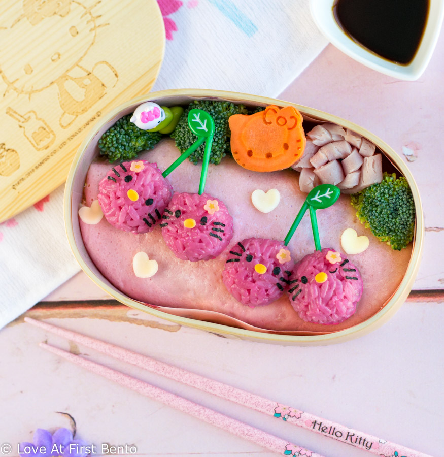 Hello Kitty Cherry Bento Box - The perfect lunch for any Hello Kitty fan, this pink & girly bento is so easy to make, it's nearly foolproof, making it perfect for beginner bento makers. Along with step-by-step instructions & video tutorial, find out the amazing tool I use to easily shape perfectly circular rice balls in just 30 seconds!! | loveatfirstbento.com [character bento, kyaraben, charaben, vegetarian]