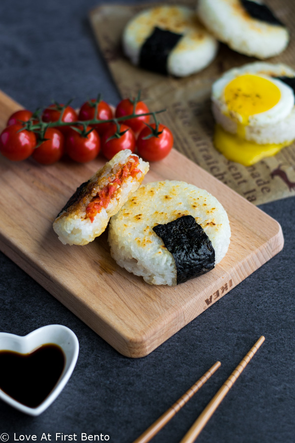 Roasted Tomato Yaki Onigiri with Fried Egg - The ultimate in lunchtime decadence! Toasty golden rice, sweet roasted tomatoes, and a runny fried egg transform your average rice ball into an irresistibly mouth-watering treat! Find out the one common kitchen tool used to make these circular onigiri - I guarantee it's in your kitchen drawers right now! Get this delicious & easy recipe at loveatfirstbento.com | bento box, Japanese food, vegetarian