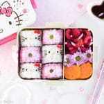 Hello Kitty Sushi Bento - Beautify your lunch with this Hello Kitty Sushi Bento! Filled with adorable Hello Kitty sushi rolls, as well as pink gingham flower sushi rolls, this pretty bento box is an edible dream come true for any Hello Kitty fan! Find out just how easy it is to make by visiting loveatfirstbento.com [character bento, kyaraben, deco sushi]